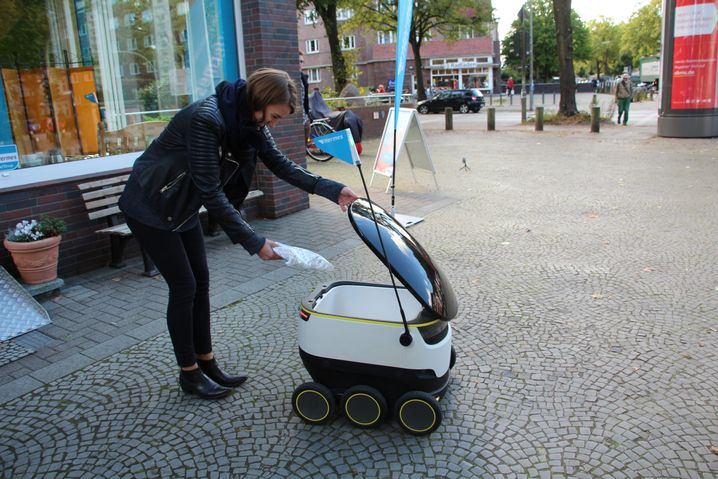 Hermes-Mitarbeiterin bepackt den Roboter