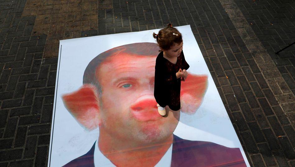 Hat mittlerweile viele Gegner in der muslimischen Welt: Emmanuel Macron, hier auf einem Poster, das auf einer Demo im palästinensischen Westjordanland gezeigt wurde (Archiv)