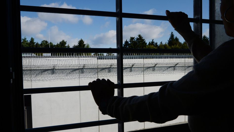 Häftling am vergitterten Fenster einer Zelle
