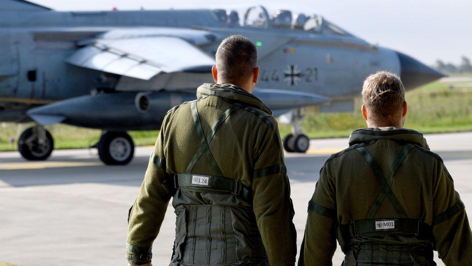 Ein Fluglehrer und ein Flugschüler stehen auf dem Fliegerhorst Jagel, während ein Tornado zum Start rollt (Symbolbild)