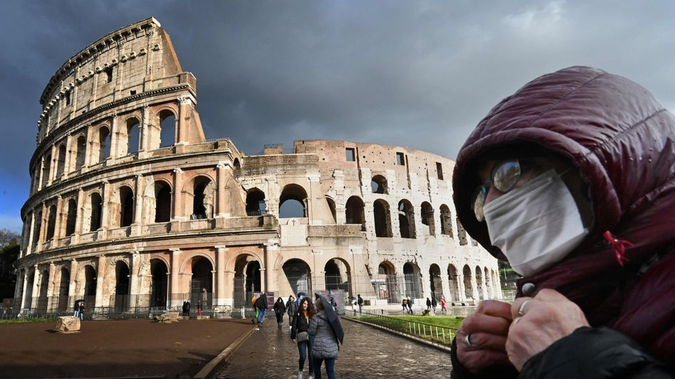 A man with a face mask in front of the Colosseum in Rome.