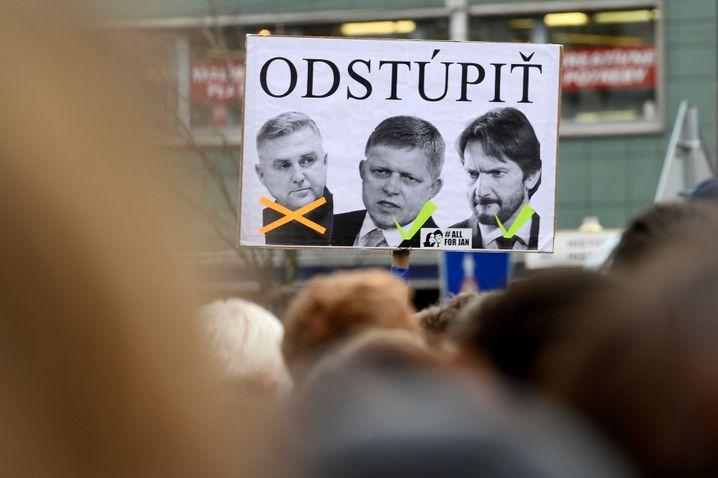 Auf dem Plakat wird der Rücktritt des Polizeipräsidenten Tibor Gaspar (links) gefordert. Die anderen beiden Männer auf dem Plakat sind Ex-Premier Robert Fico (Mitte) und der ehemalige Innenminister Robert Kalinak (rechts).