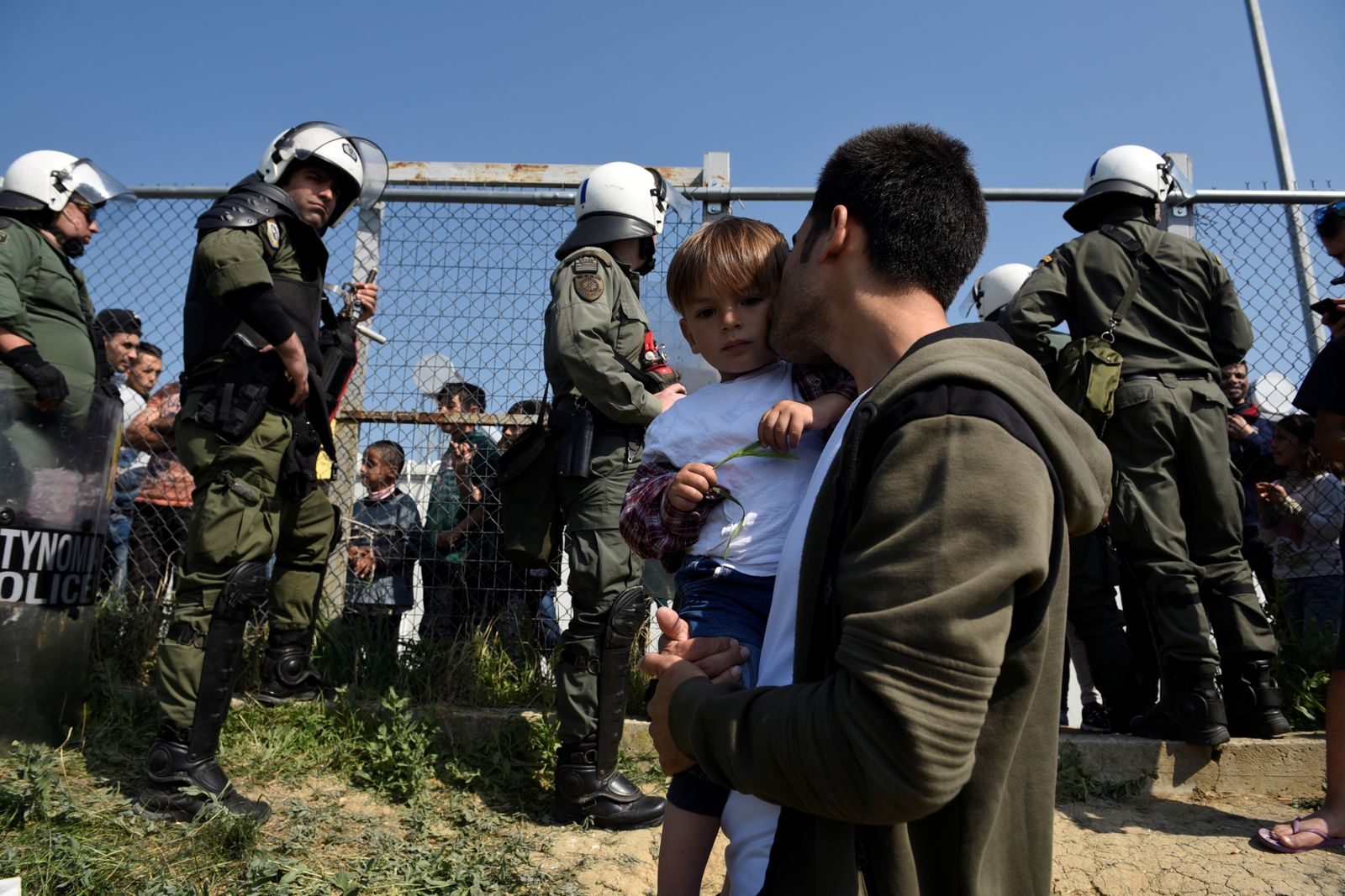 A man holds a child as he stands in front of a riot police cordon next to a camp in the town of Diavata in northern Greece