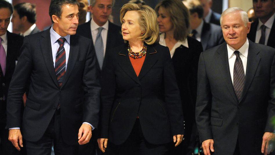 US Secretary of State Hillary Clinton (C) walks with NATO Secretary-General Anders Fogh Rasmussen (L) and US Defense Secretary Robert Gates