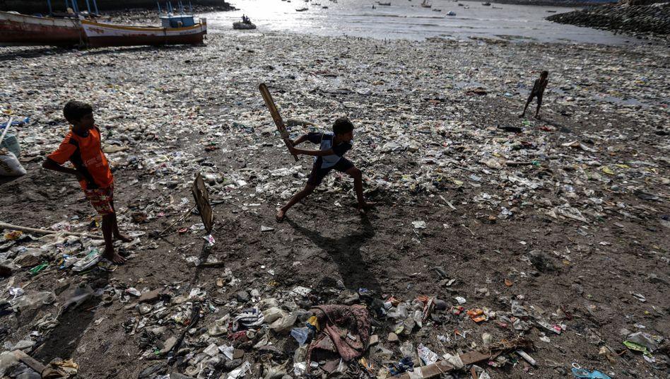 Kinder spielen an einem Strand in Indien in angespültem Plastikmüll