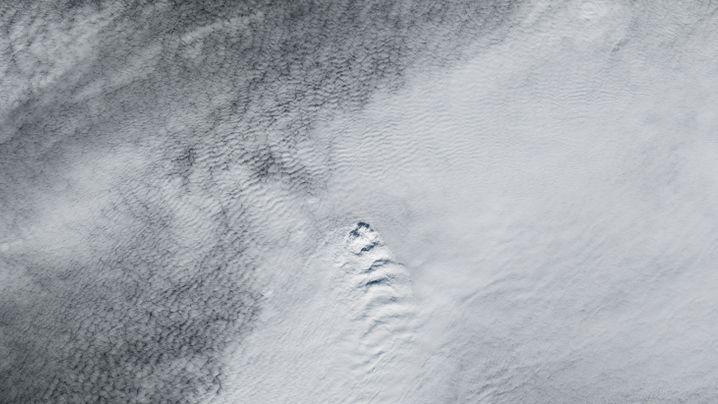 Das Schiebebild zeigt links die Wolkenformation, genau darunter befindet sich der Vulkan Fagradalsfjall (roter Punkt im rechten Bild)