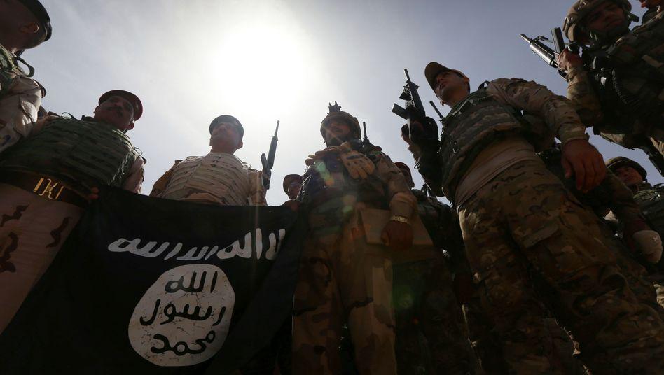 Irakische Soldaten mit einer eroberten IS-Flagge