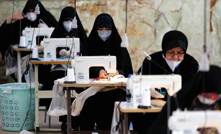 Women sew masks at a textiles factory in Iran