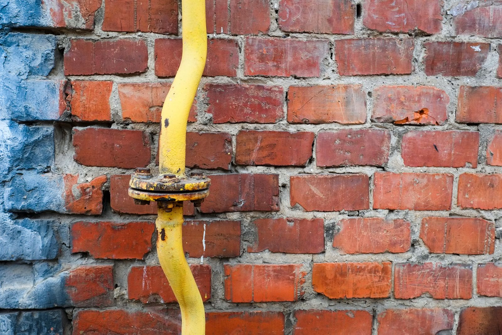 Yellow pipeline against brick wall