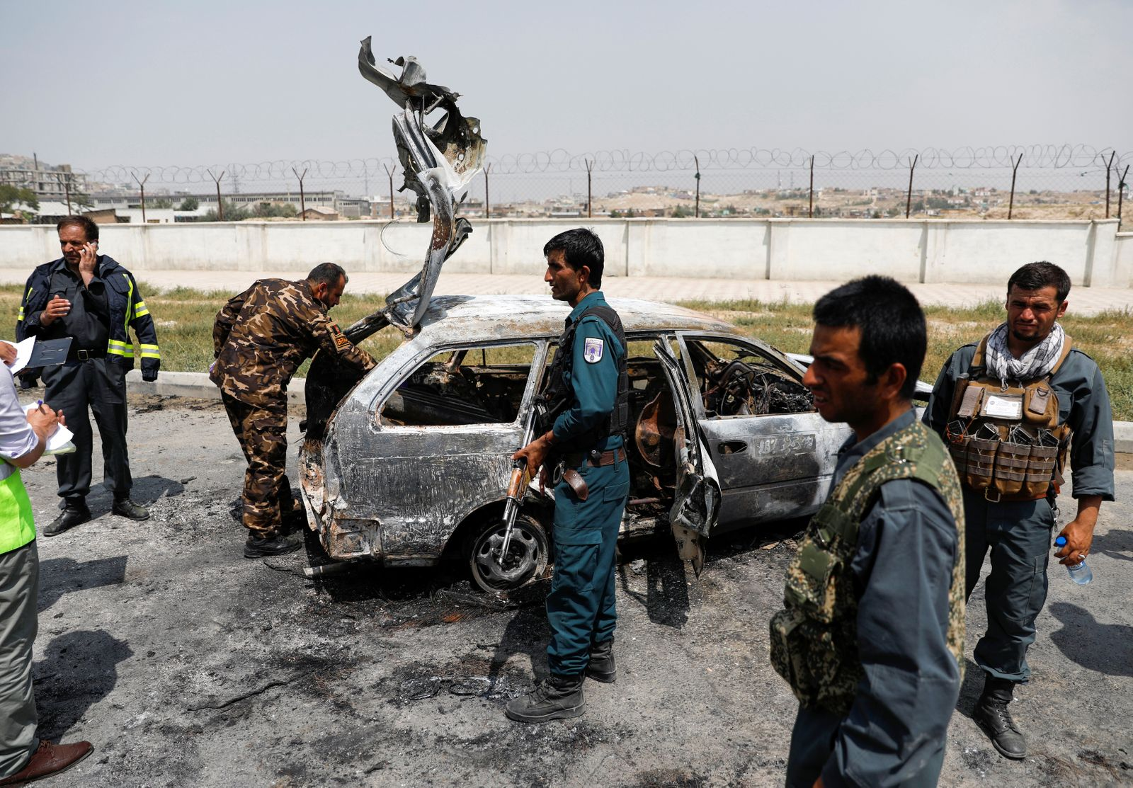 Afghan police officers inspect a vehicle from which insurgents fired rockets, in Kabul