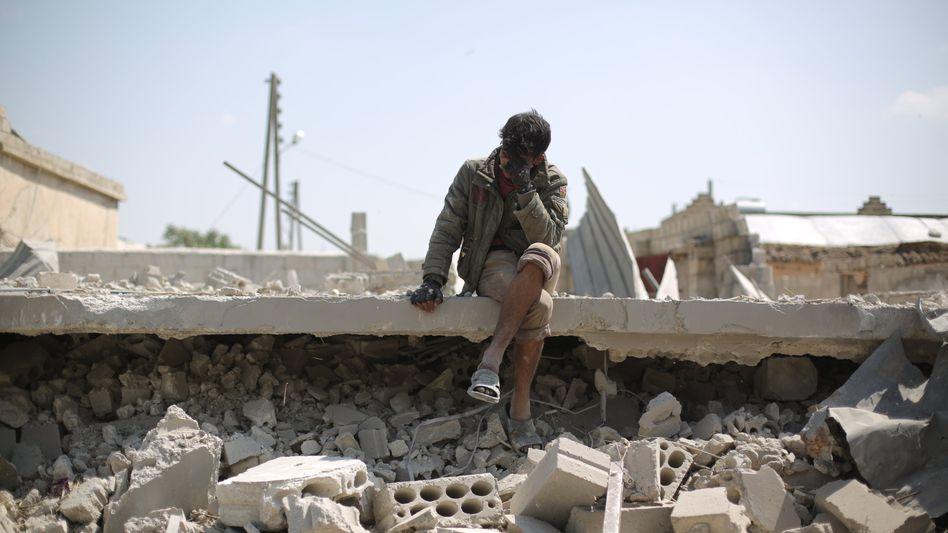 Ein Mann verdeckt mit seiner Hand das Gesicht, während er nach einem Luftangriff zwischen zerstörten Gebäuden sitzt
