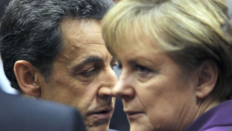 French President Nicolas Sarkozy speaks with German Chancellor Angela Merkel during the EU summit in Brussels.