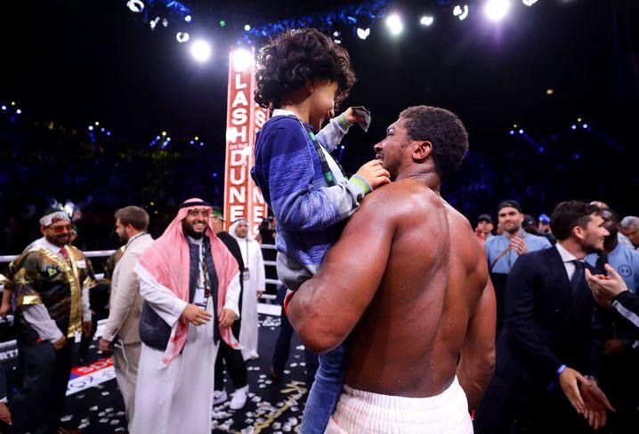 Man kennt sich, man mag sich, man zahlt sich Millionen: Anthony Joshua feiert seinen Sieg mit dem Sohn von Prinz Khalid Bin Abdulaziz Al Saud auf dem Arm