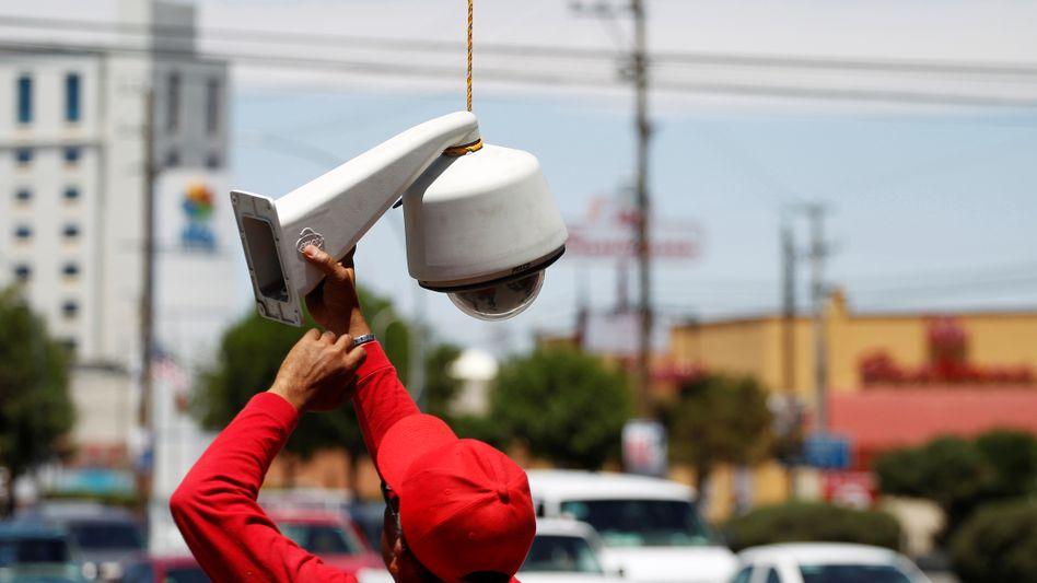 Ein Techniker überprüft eine Kameraanlage in der mexikanischen Grenzstadt Ciudad Juárez. Auch Drogenkartelle installieren eigene Kameras in Städten