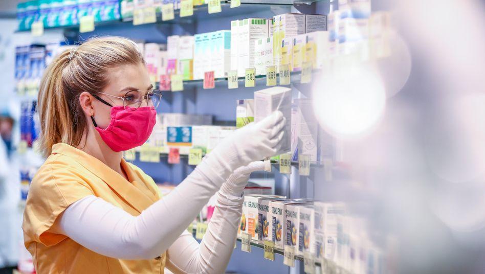 Mitarbeiterin einer Apotheke mit Mundschutz