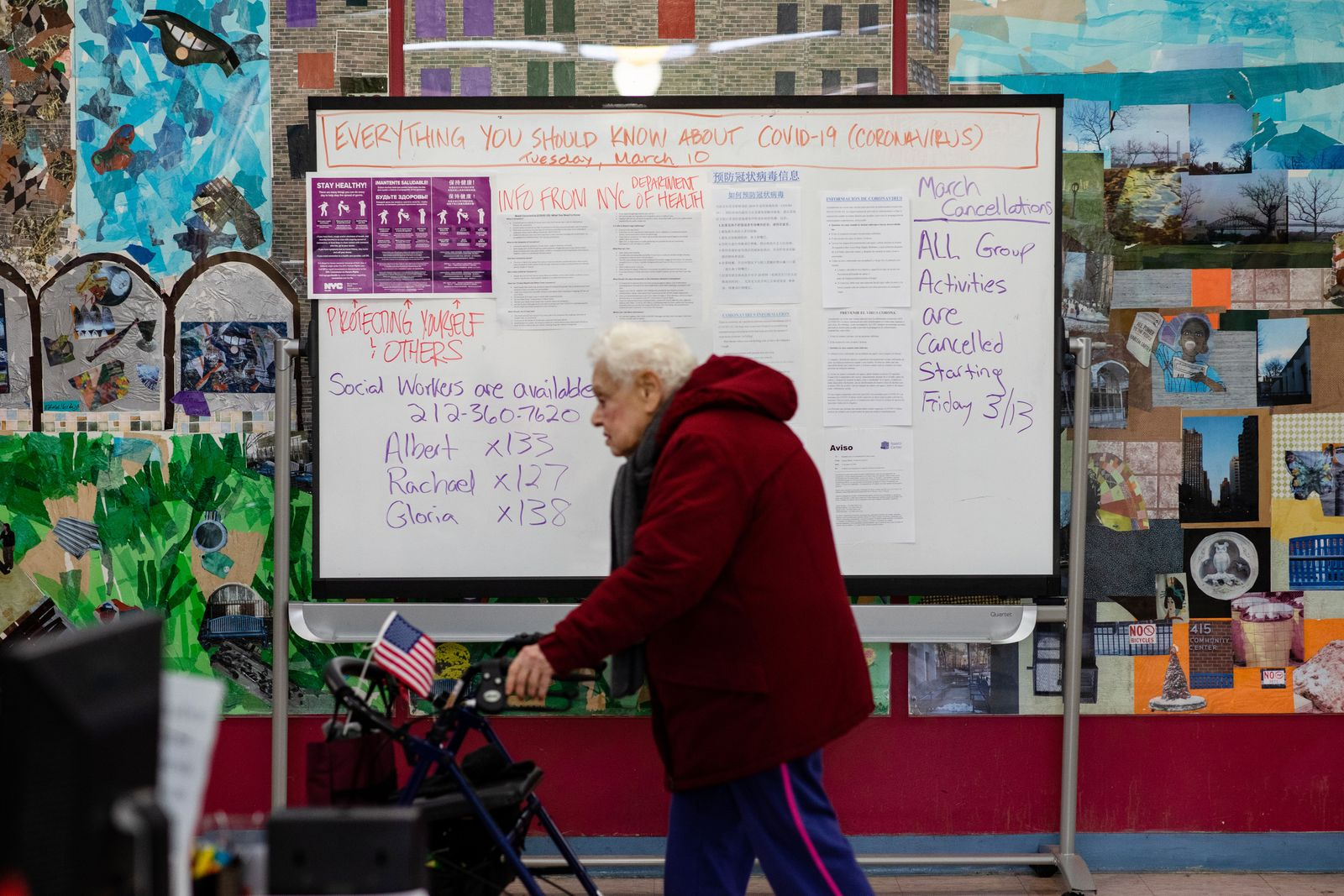 A person walks through the Stanley Isaacs Center past a board with information about the coronavirus, in Manhattan, Tuesday, March 17, 2020. (Stephen Speranza/The New York Times)