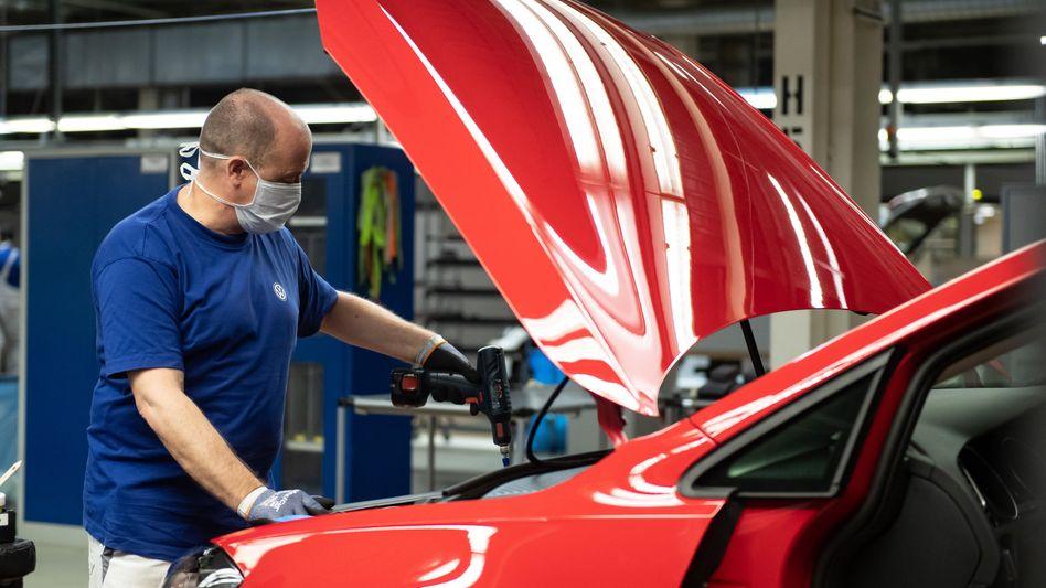 VW-Mitarbeiter bei der Produktion eines Autos