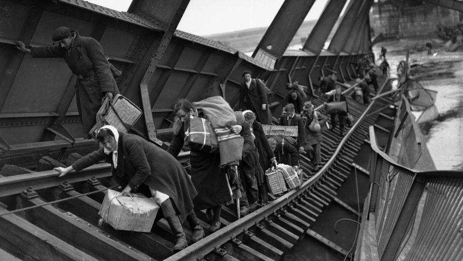 Vertriebene auf dem Weg in den Westen überqueren im Mai 1945 die Elbe bei Tangermünde auf einer von den Deutschen zerstörten Brücke