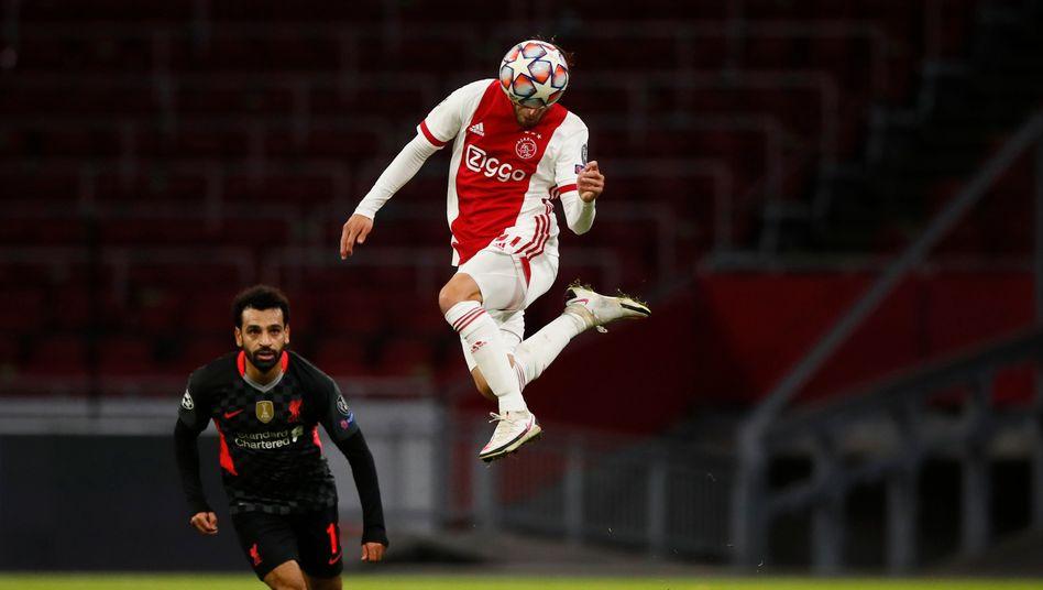 Liverpools Mohamed Salah (l.) staunt über die Sprungkraft von Ajax-Verteidiger Nicolas Tagliafico, der den einzigen Treffer des Tages erzielte - nur ins eigene Tor