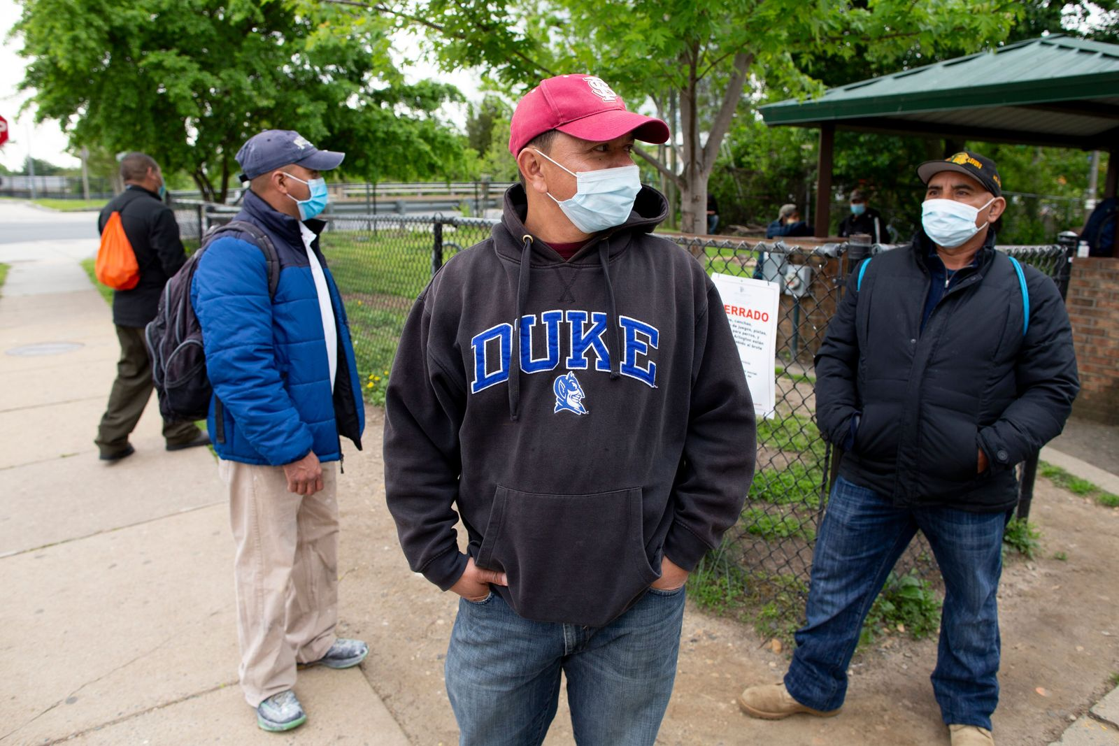 Day laborers wait for jobs at a hiring site at a park in Shirlington, Virginia, USA - 08 May 2020