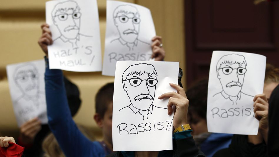 "Demonstrators at a Potsdam, Germany, reading held by Thilo Sarrazin hold up protest signs with the German spelling for ""racist."" This opinion, however, has not been universal here."