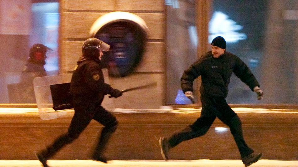 Proteste gegen Wahlfälschung: Ein weißrussischer Polizist jagt im Dezember 2010 einen Demonstranten