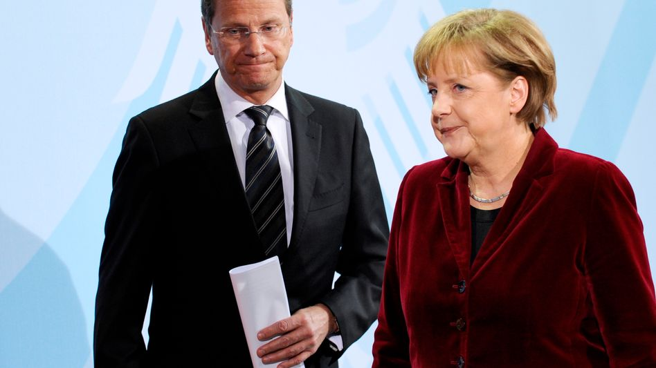 """German Chancellor Angela Merkel (right) and Foreign Minister Guido Westerwelle (left) after announcing a three-month """"moratorium"""" on the extension of nuclear power plant lifespans."""
