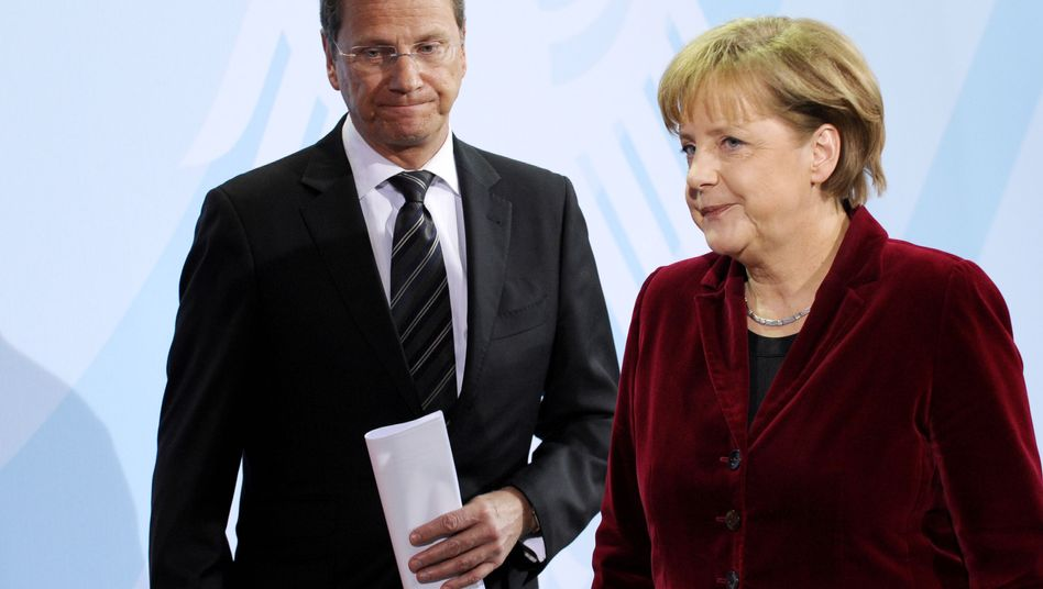 "German Chancellor Angela Merkel (right) and Foreign Minister Guido Westerwelle (left) after announcing a three-month ""moratorium"" on the extension of nuclear power plant lifespans."