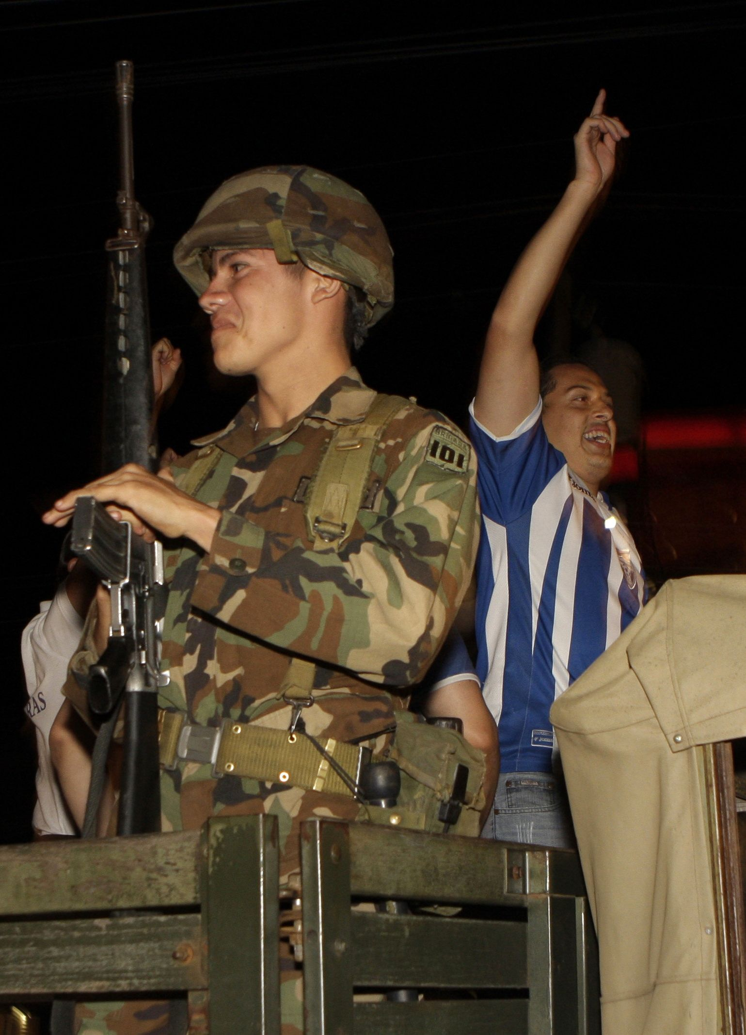 Honduras-fan feiert, Militär davor