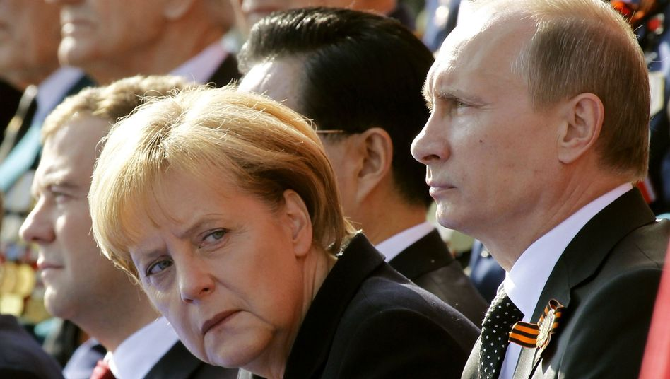 Merkel (with Dmitry Medvedev, left, and Vladimir Putin, right): The situation is business as usual, but boredom is creeping into the relationship.
