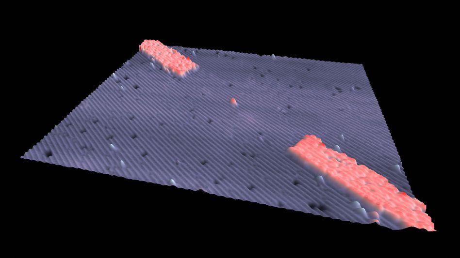 Atom-Transistor (Rastertunnelmikroskop-Aufnahme): Der rote Punkt in der Mitte ist das Phosphoratom, die Elektroden sind ebenfalls rot dargestellt