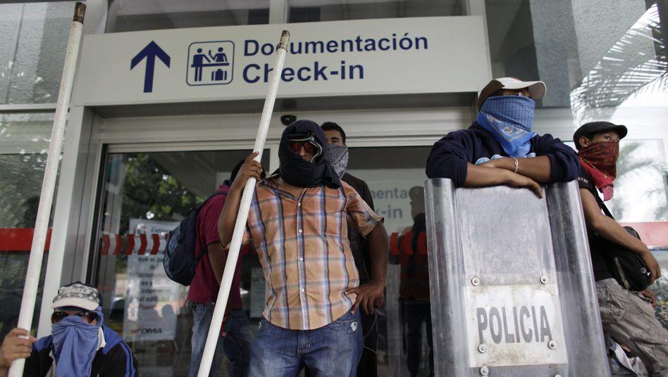 Warten auf Polizisten: Bewaffnete Demonstranten am Flughafen von Acapulco