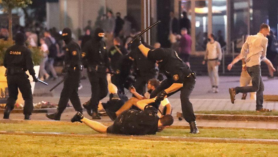Ein Sicherheitsbeamter schlägt in Minsk auf einen Demonstranten ein