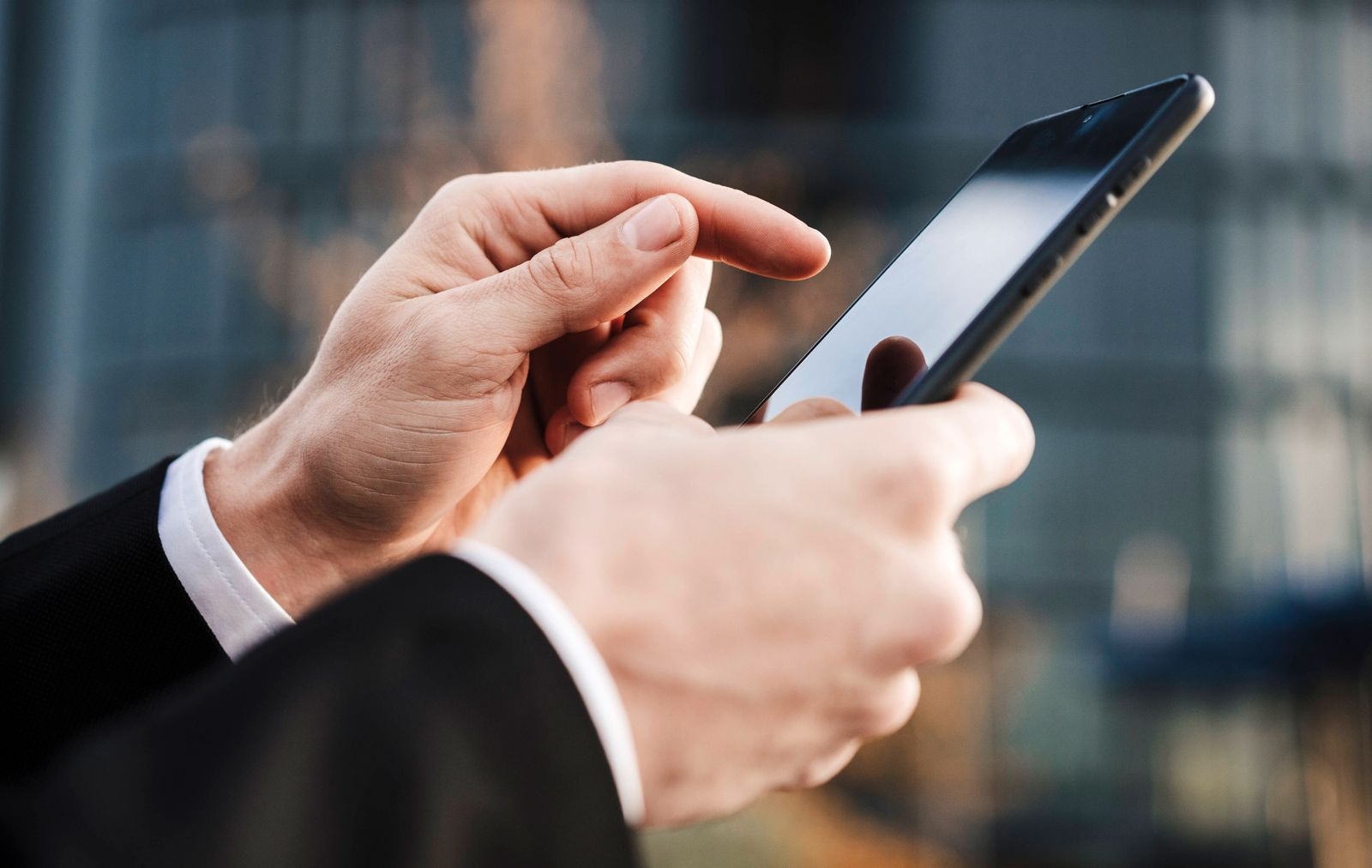 Close-up of businessman using smart phone outdoors model released Symbolfoto EBBF02022