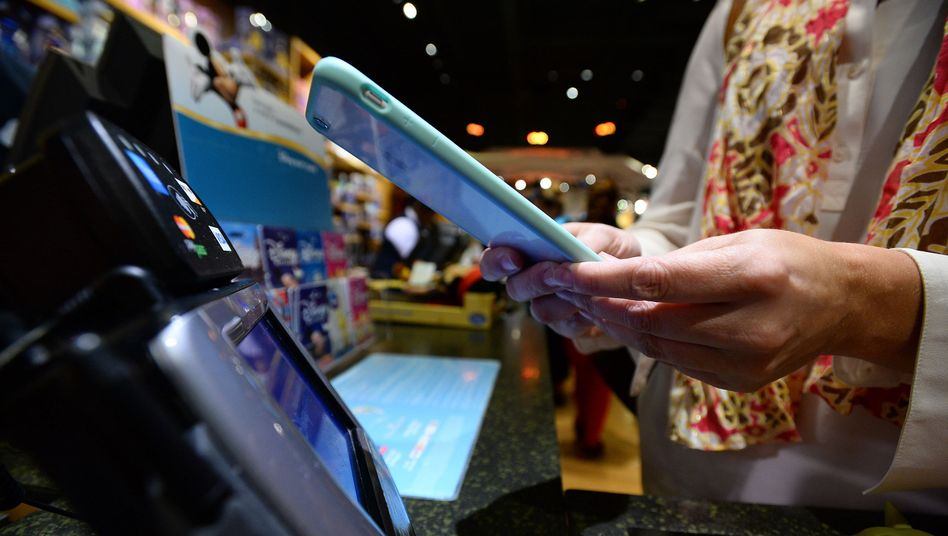 Apple-Pay-Bezahlvorgang: Handy über den Scanner, Finger auf den Sensor