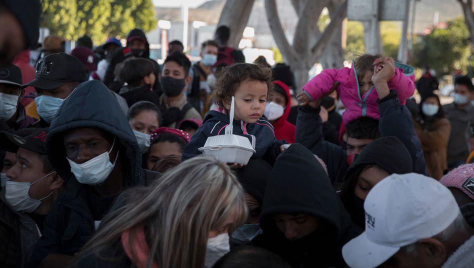 Zahlreiche Menschen warten am Grenzübergang vom mexikanischen Tijuana in die US-Stadt San Diego auf eine Mahlzeit