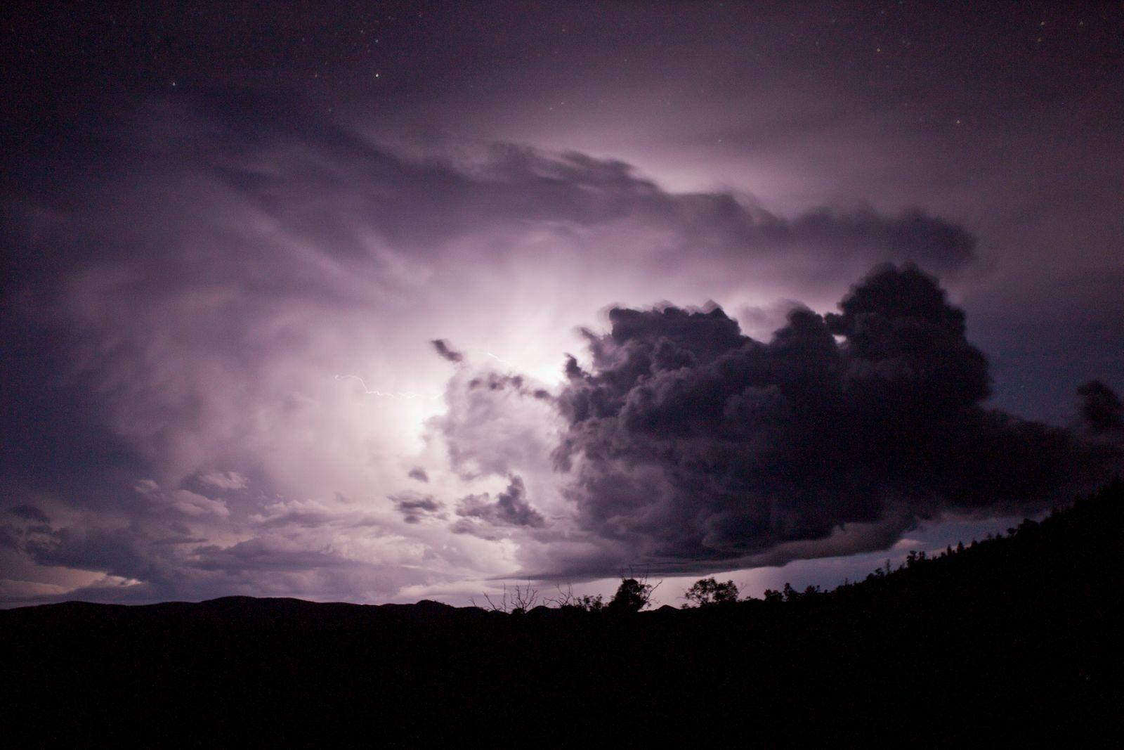 Lightning flash behind a cloud at night