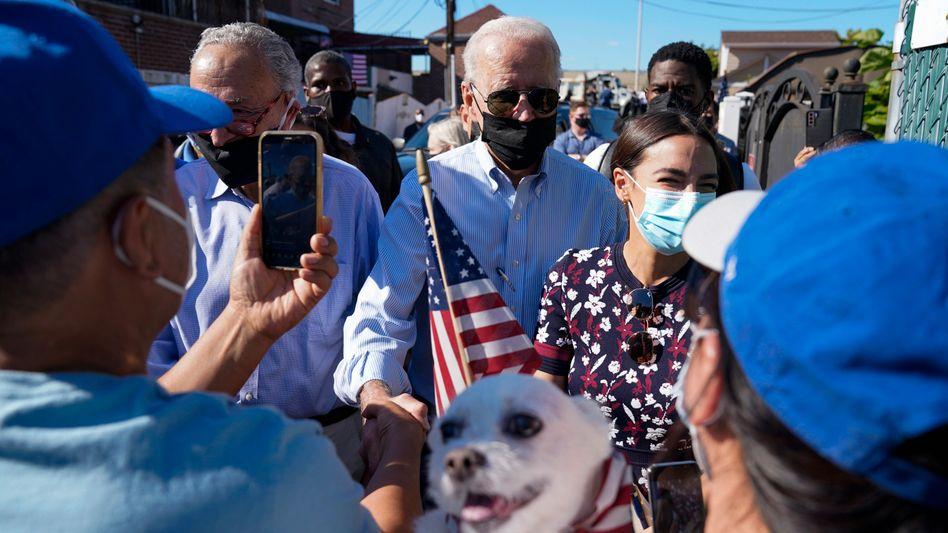 Joe Biden (M.) im New Yorker Stadtteil Queens. Beim Besuch des US-Präsidenten waren auch der Mehrheitsführer des Senats, Chuck Schumer, sowie die Abgeordnete Alexandria Ocasio-Cortez dabei