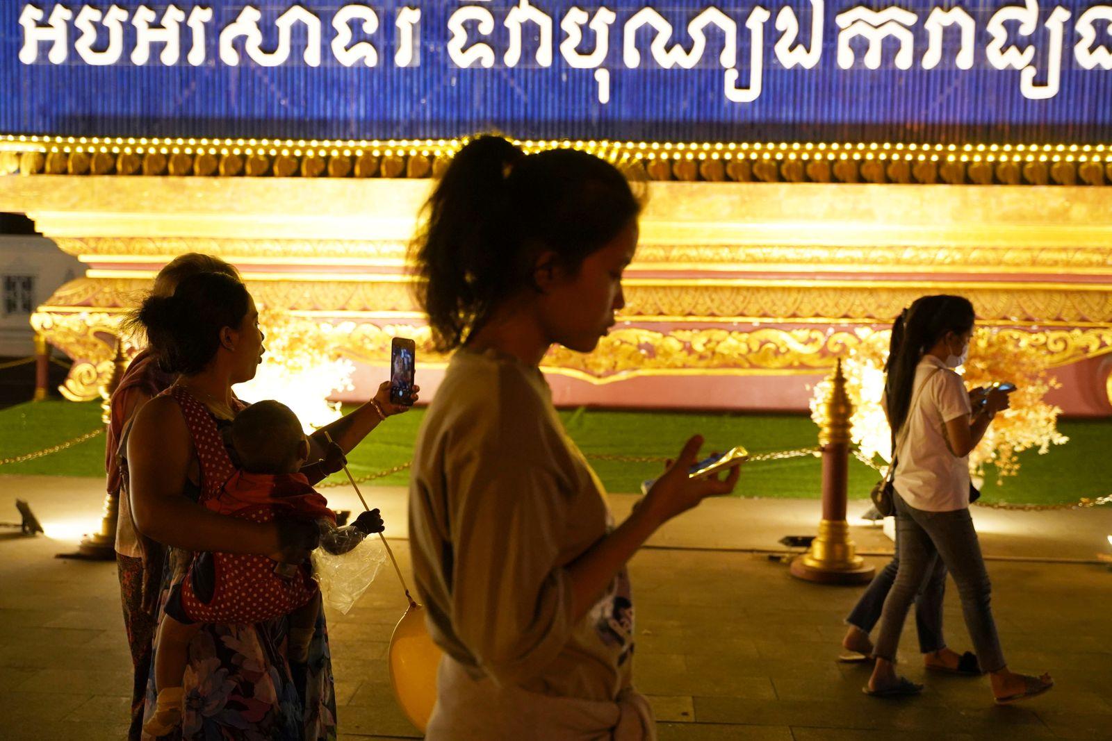 People walk using their mobiles phones in Phnom Penh