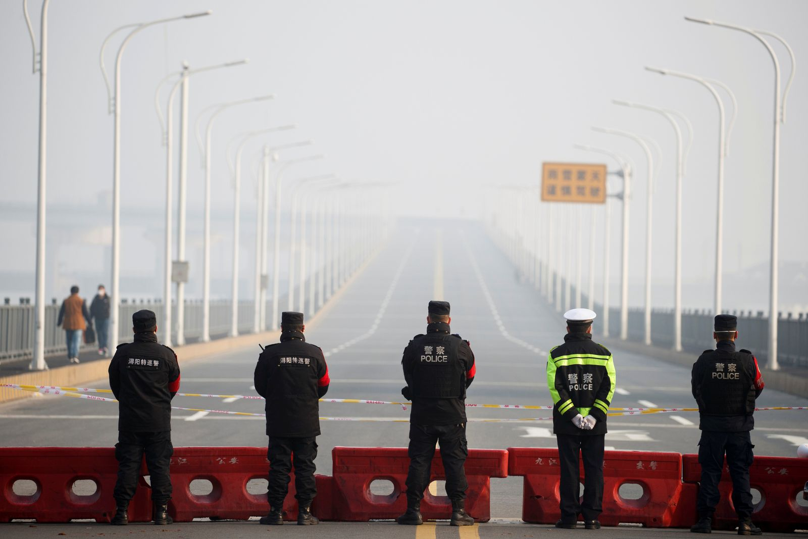Police stand at a checkpoint at the Jiujiang Yangtze River Bridge that crosses from Hubei province in Jiujiang