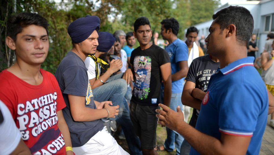 Flüchtlinge beraten sich in Leipzig vor einer Sporthalle: Sie wird vorübergehend zur Unterbringung genutzt