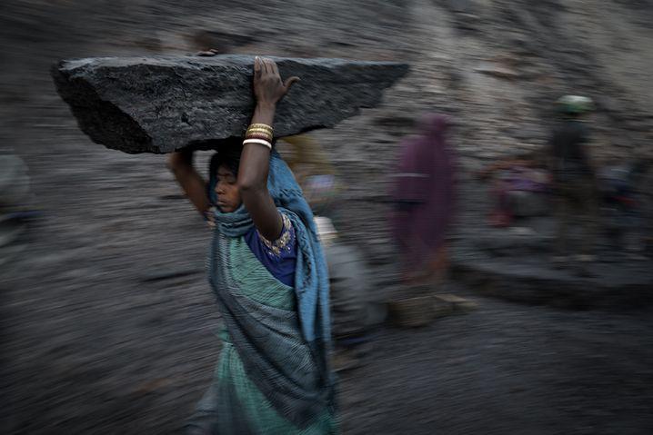 Eine Frau trägt ein riesiges Stück Kohle durch die Asche