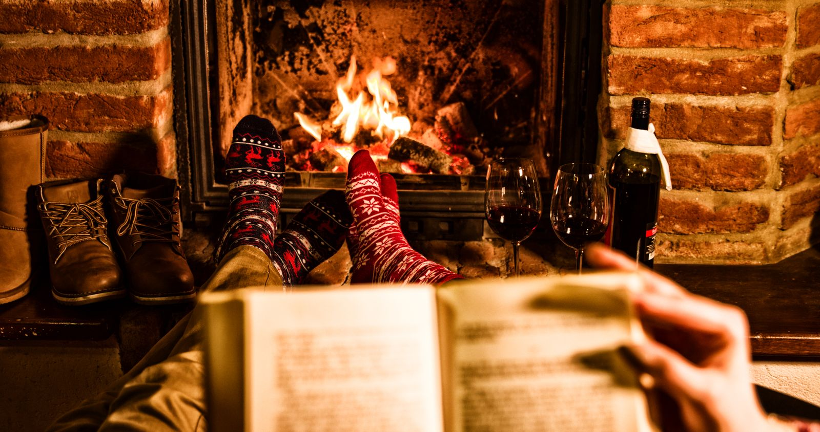 Couple with book resting by fireplace during Xmas