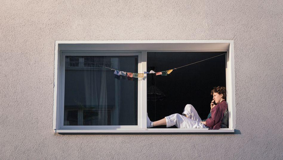 Eine junge Frau sitzt in ihrem Fenster, Köln