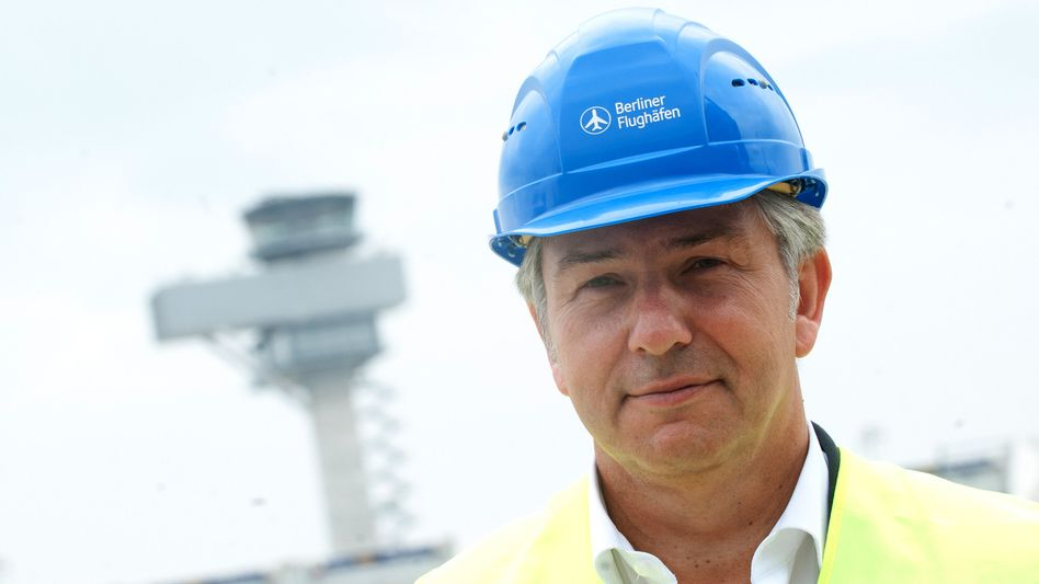 Berlin Mayor Klaus Wowreit wears a hardhat as he visits the construction site of the city's new BER airport.