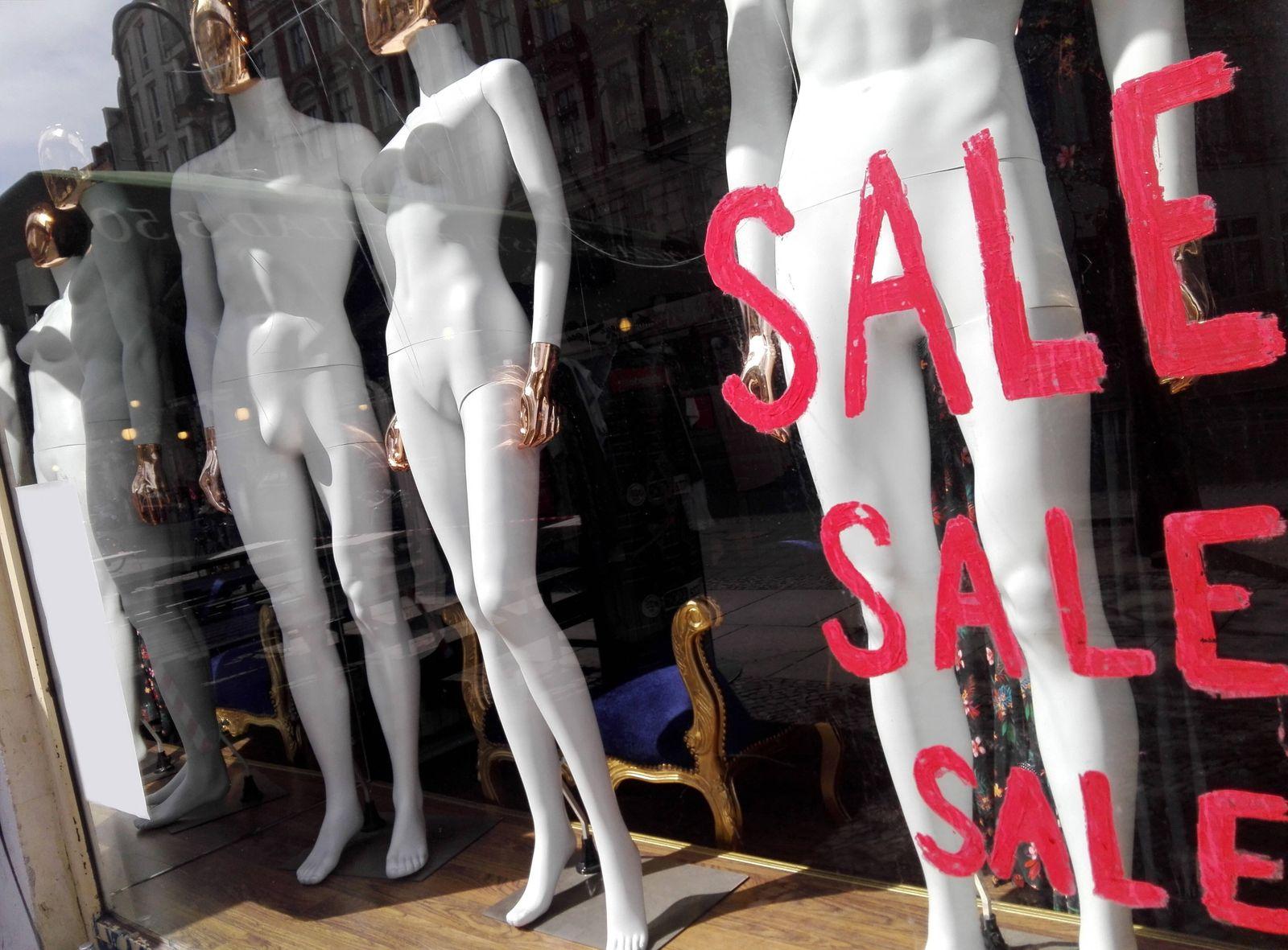 15.04.2020, Berlin - Deutschland. Schaufenster eines Ladens mit nackten Schaufensterpuppen und dem Schriftzug Sale, ein
