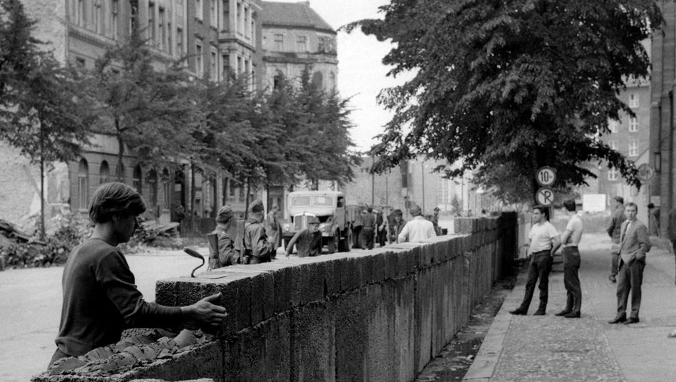 Workers build the Wall under the watchful eye of East German police in 1961.