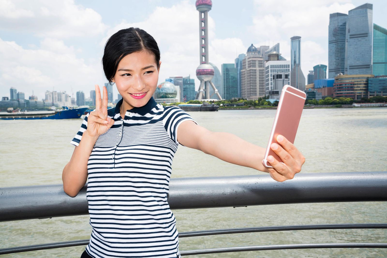 Beautiful woman gesturing peace sign while taking selfie through smart phone against Pudong skyline,model released, Symb