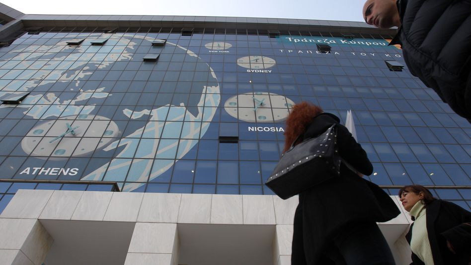 Pedestrians pass the headquarters of Greek operations of the Bank of Cyprus in Athens.