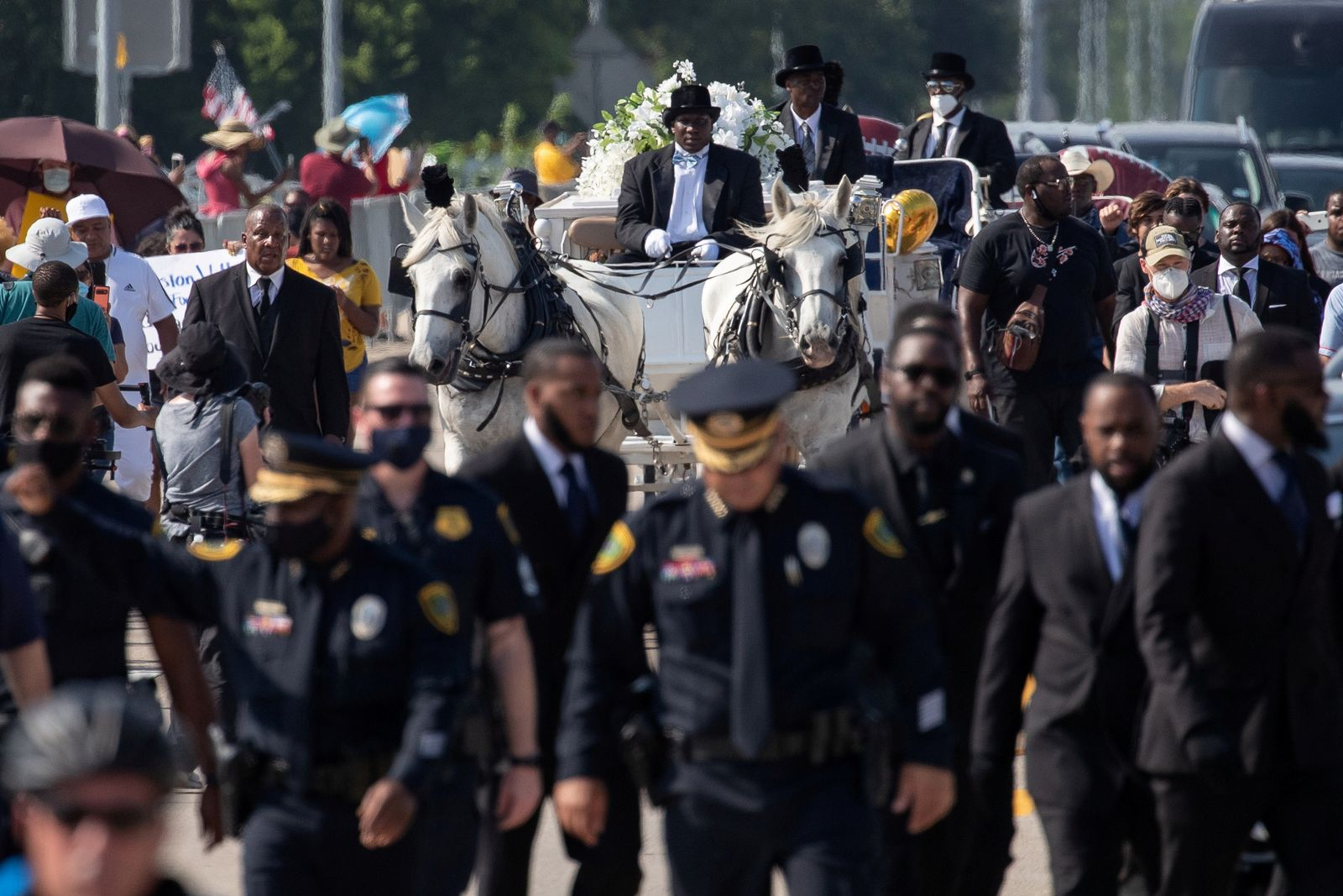 Officers lead the horse drawn carriage with coffin of George Floyd as it enters cemetery ahead of burial in Pearland, Texas